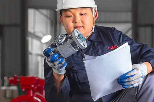 Worker inspecting a ball valve
